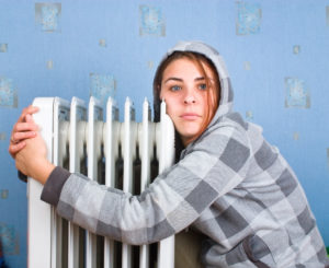 girl hugs a water filled radiator inside her house trying to keep warm